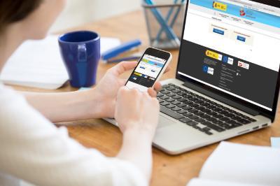 Imagen en la que aparece una mesa con un ordenador y los brazos de una persona apoyada en ella